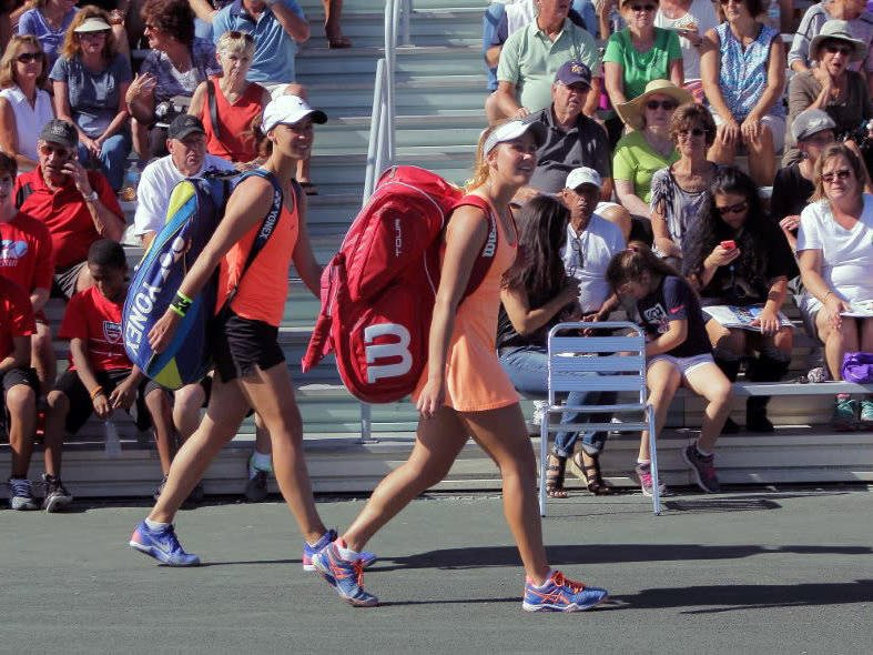 Two tennis players with their bags.