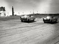 Black and white photo of early drag racers.