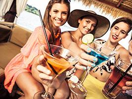 thre women holding cocktails
