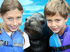 two children posing for picture with seal