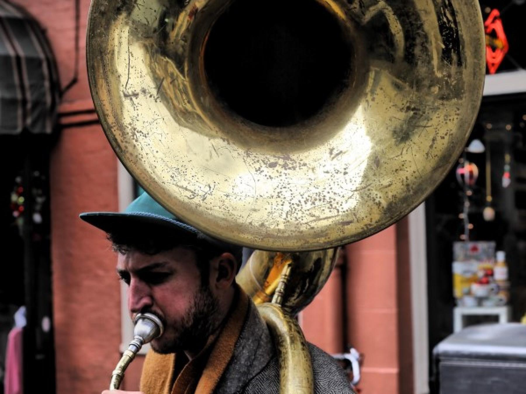 A man playing a tuba in the streets near the hotel