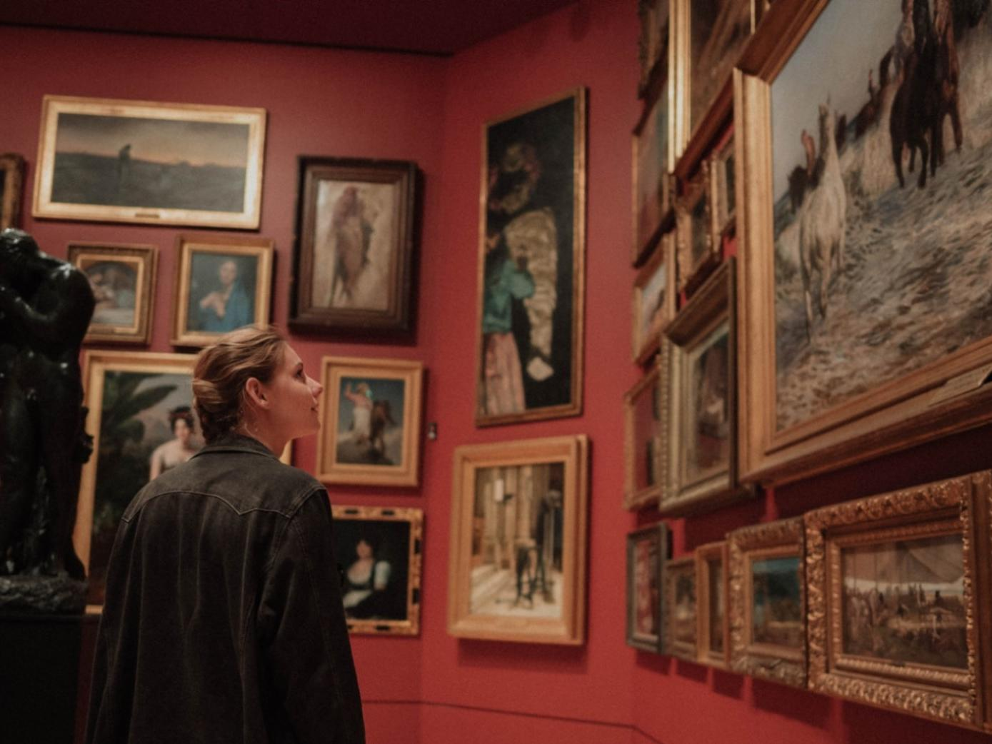 A woman looking at paintings in New Orleans Museum of Art