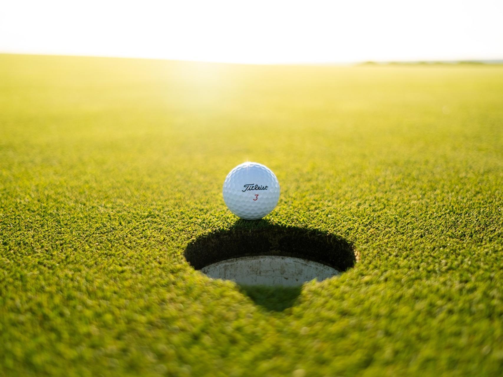 a golf ball next to a hole