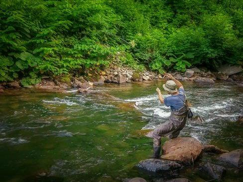A man fly fishing in the river near Chatrium Niseko Japan