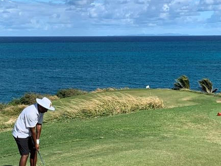 A man is playing golf at Tamarind Reef Resort