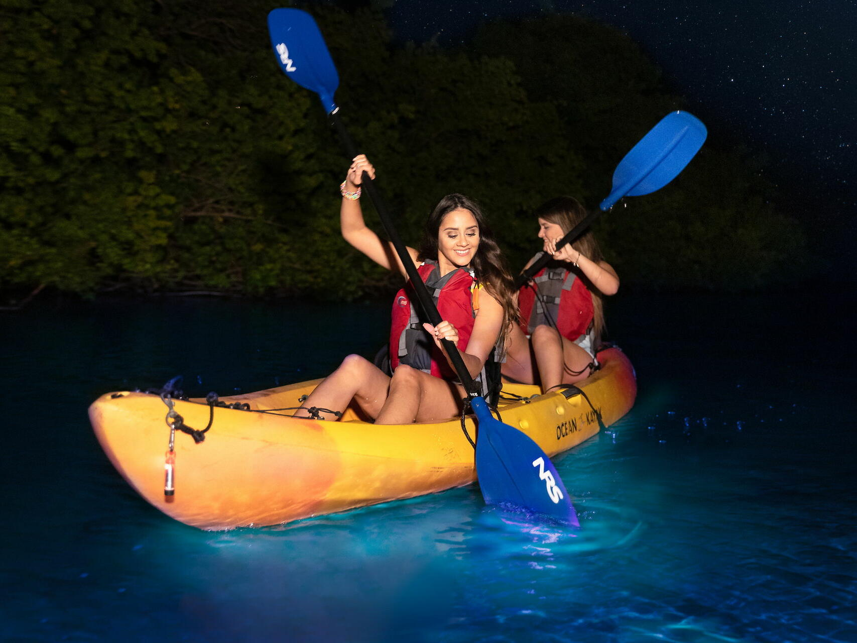 two women kayaking at night