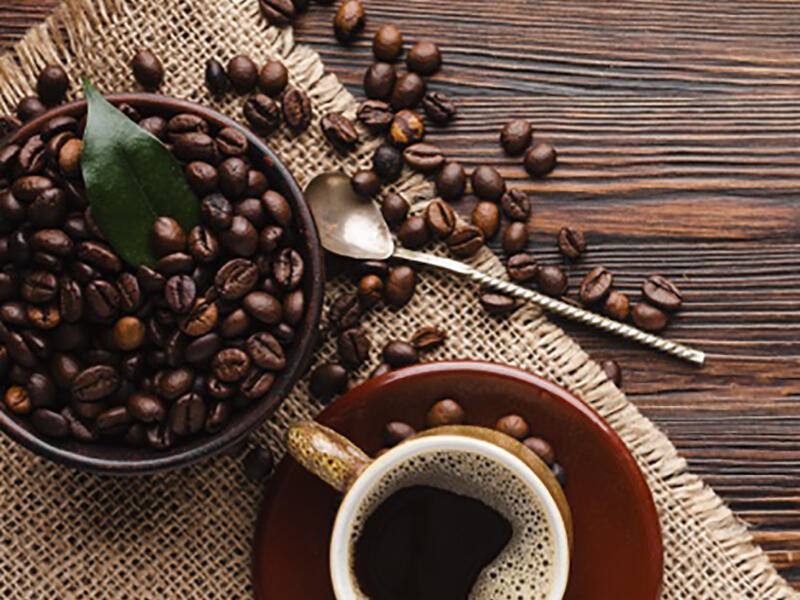 coffee beans next to cup of brewed coffee