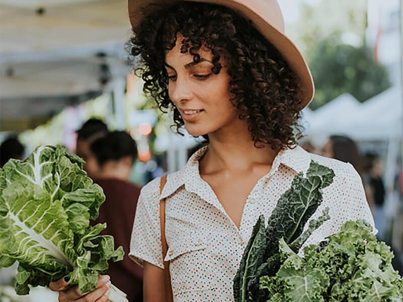 woman holdin vegerables at market