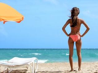 woman in bathing suit standing on beach