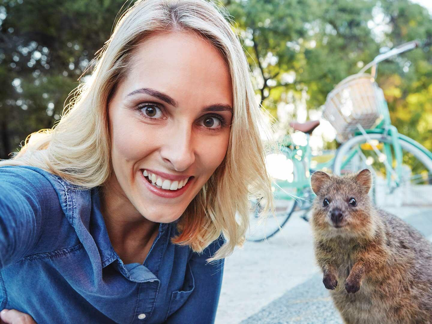 A woman taking a picture with a quokka at Rottnest Island near Be Fremantle