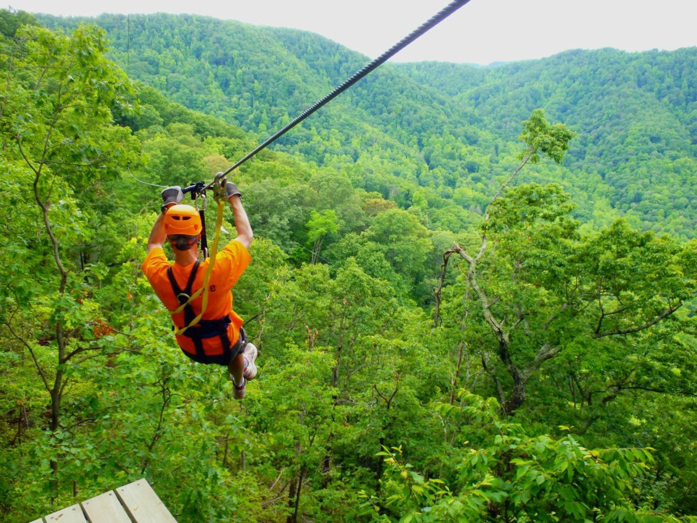 A man on a zipline at The Gorge Zipline near Mountain Inn & Suites