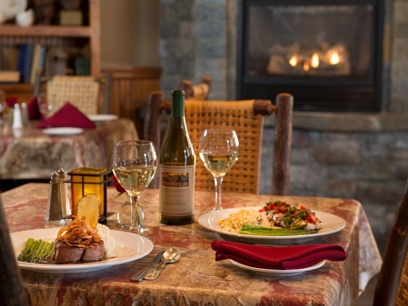 Dinner table with entrees and wine with a fireplace in the background