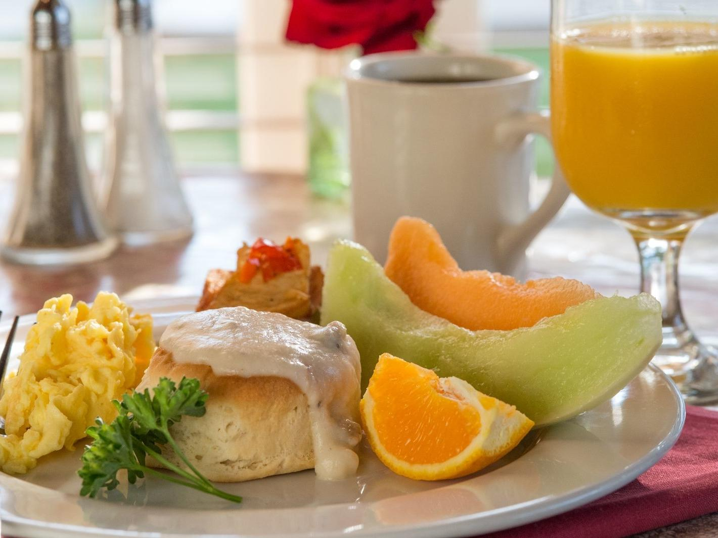 Breakfast plate with a biscuit and gravy, eggs, fruit and orange juice