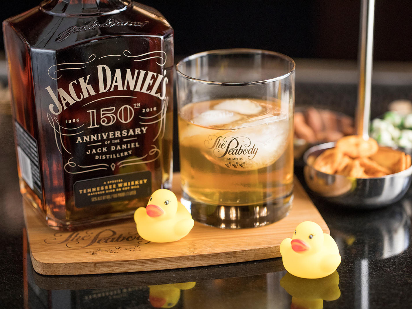 Bottle and poured glass of Jack Daniels' with rubber ducks