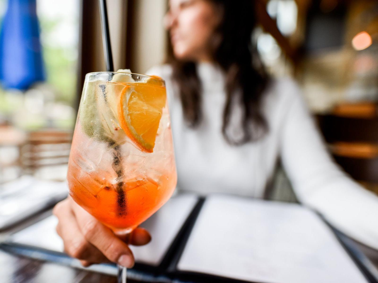 Woman holding cocktail.
