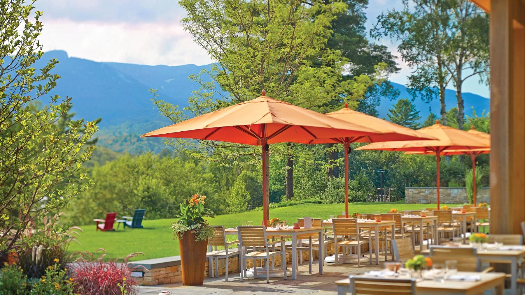Outdoor restaurant with mountainscape in background.