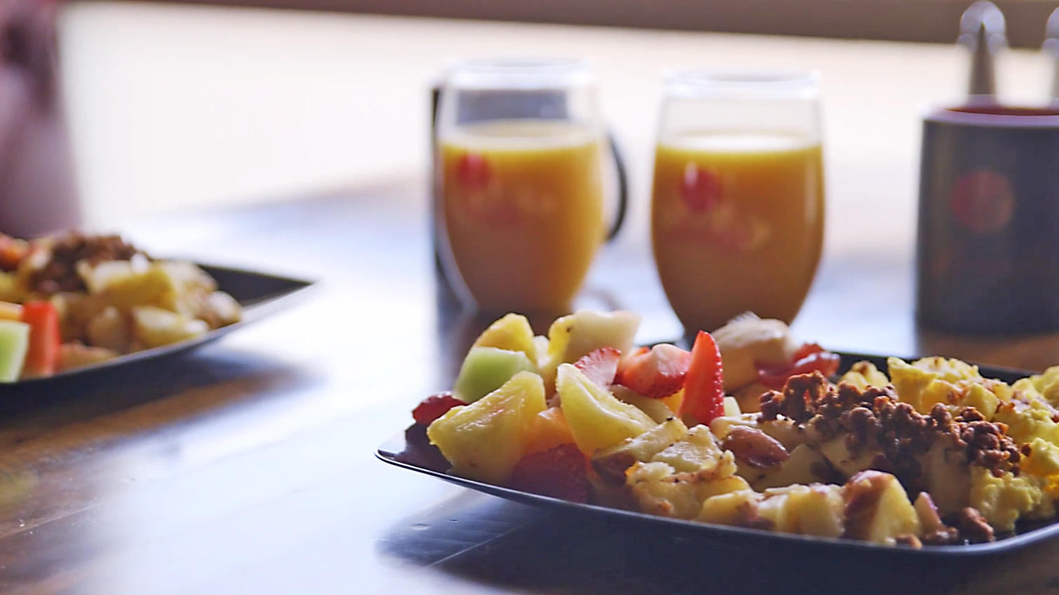 Scrambled eggs, fresh fruit and orange juice.