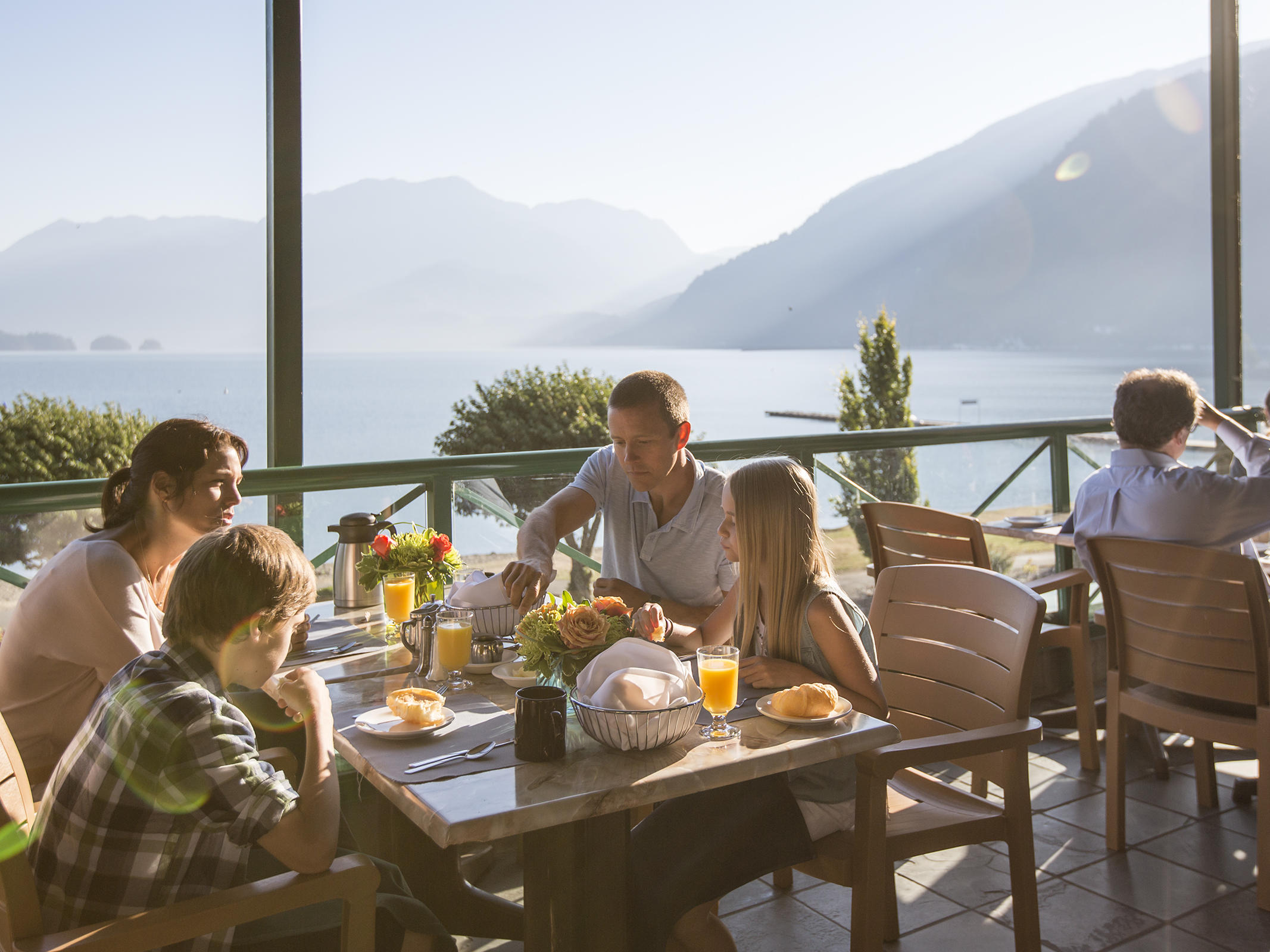 family eating outside with views of mountain and water