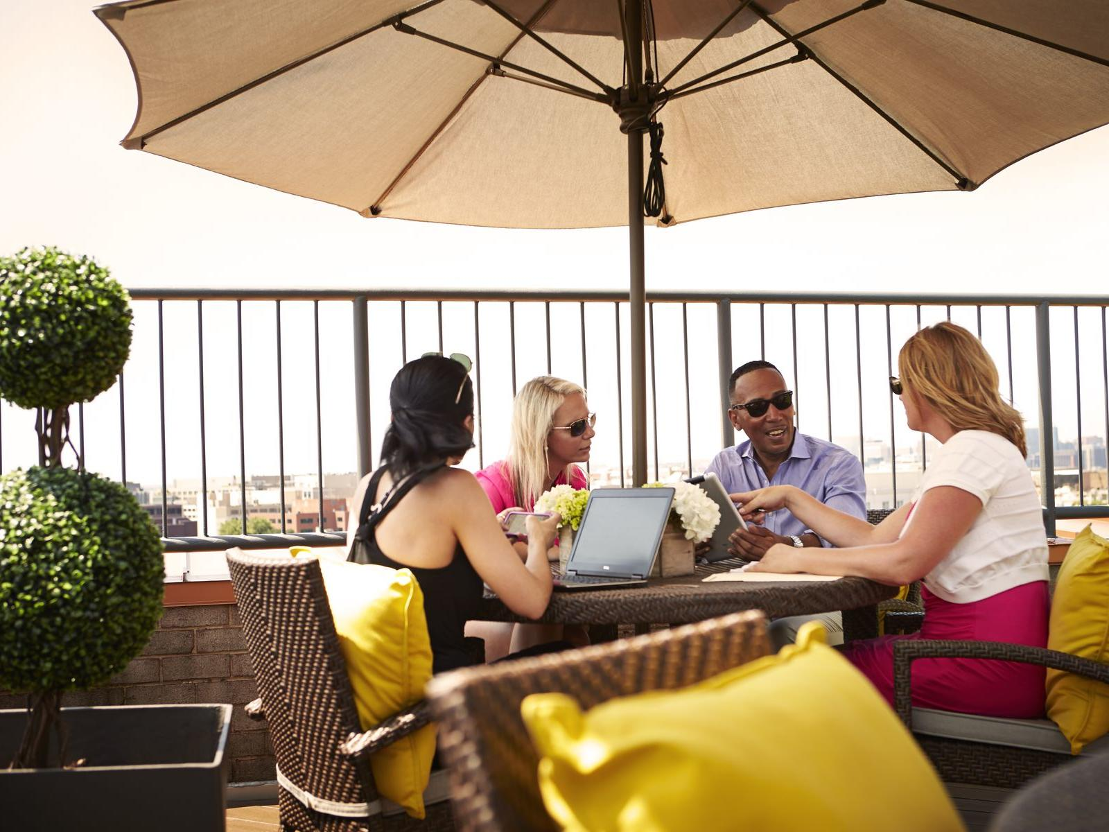 Guests working at table at the rooftop patio