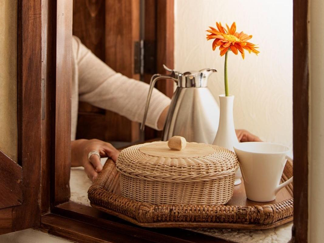 a tray with a basket, mug, and vase