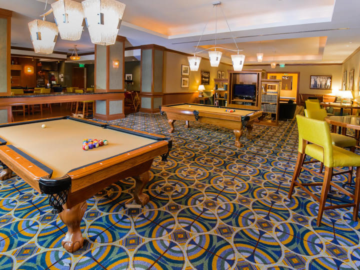 two pool tables with bar height tables and stools