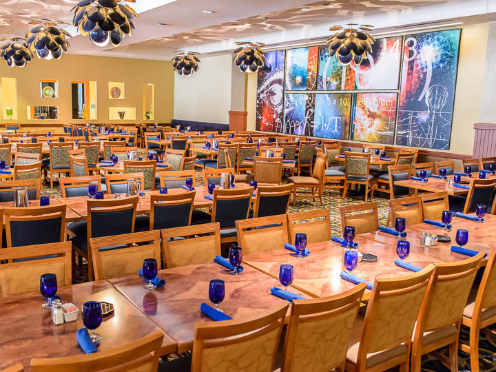 dining room with rows of dining tables and blue place settings