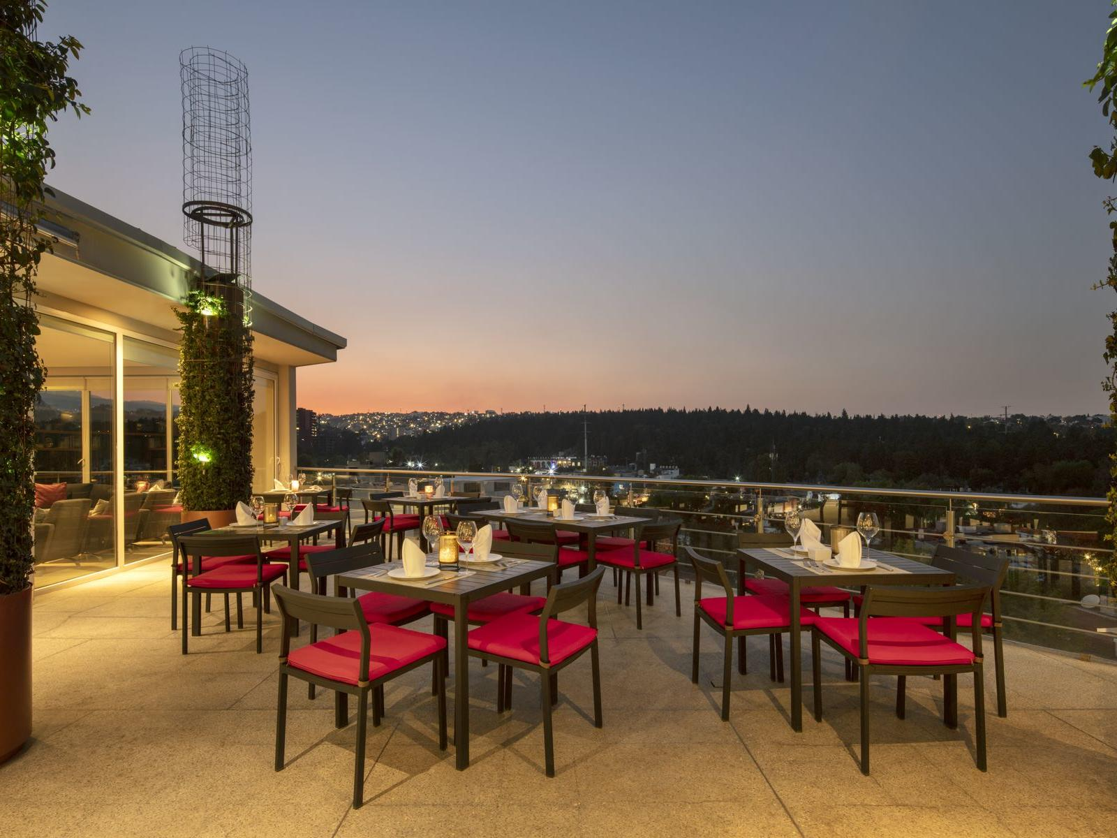 outdoor restaurant with tables and chairs overlooking hills and sunset