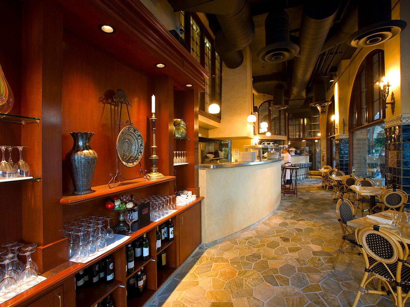 walkway in restaurant with tables and wine on shelves