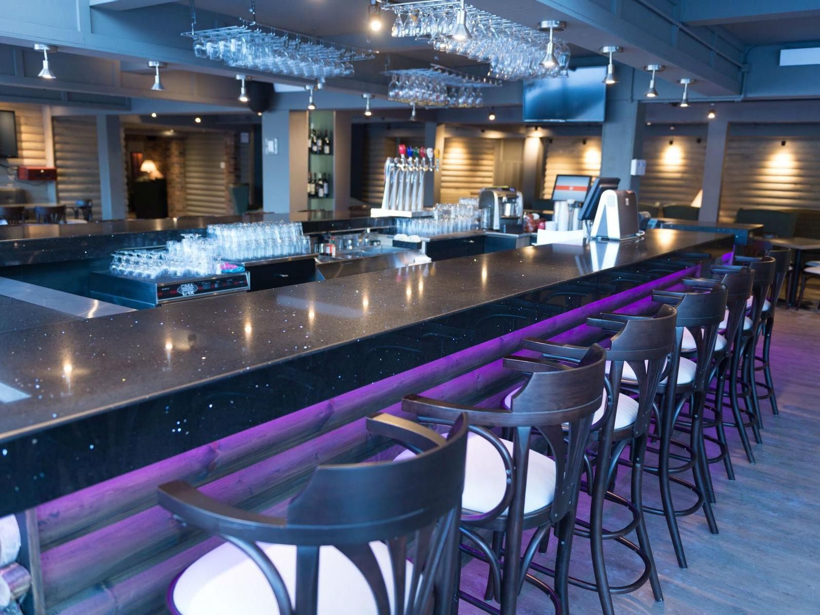Modern bar area with purple neon under lighting