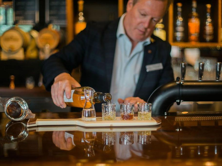 Gentleman pouring a flight of cocktails.