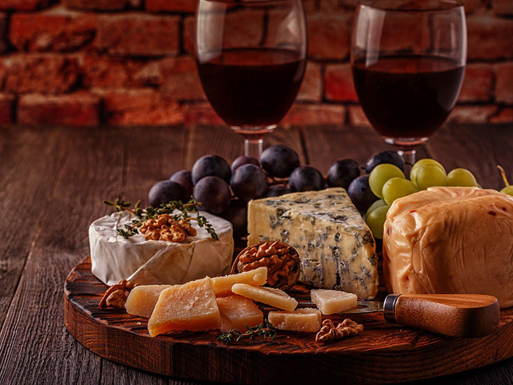 Two glasses of red wine and platter of cheeses and grapes