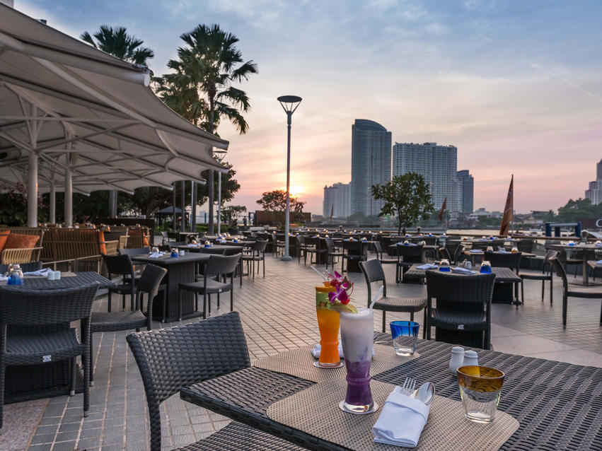 Drinks and dining outdoors besides a river view of PIER 28 at Chatrium Hotel Riverside Bangkokok