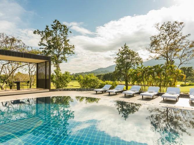 Beach lounge chairs near a pool with a tropical garden view of the pool bar at Chatrium Golf Resort Soi Dao Chanthaburi