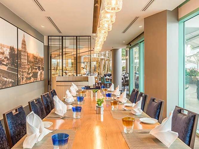 Long dining table with an elegant lighting setting of River Barge Restaurant at Chatrium Hotel Riverside Bangkok