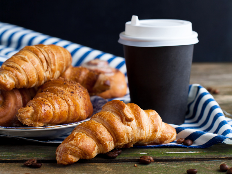 Plate of croissants and to-go cup of coffee