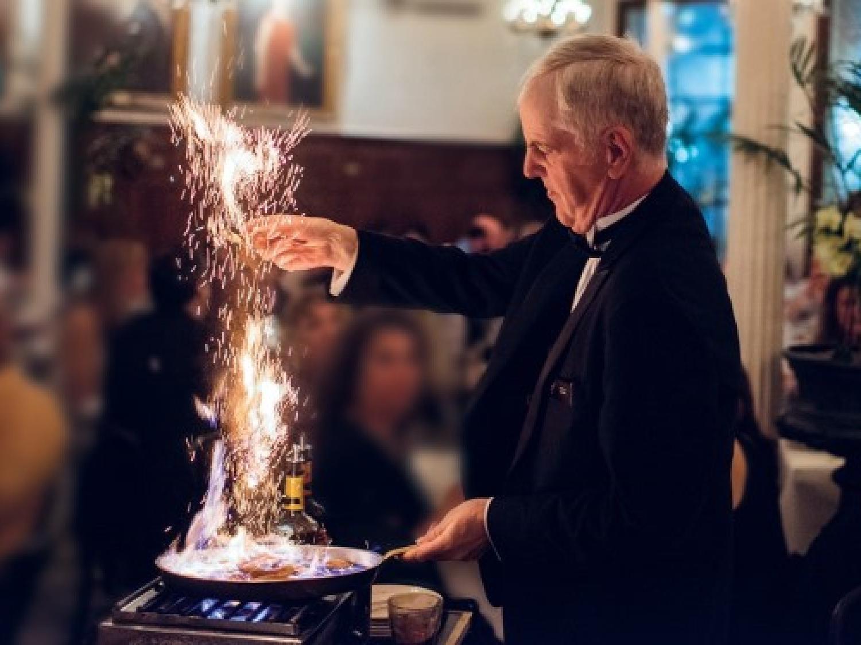 A waiter flambéing a dish at Arnaud's near St. James Hotel