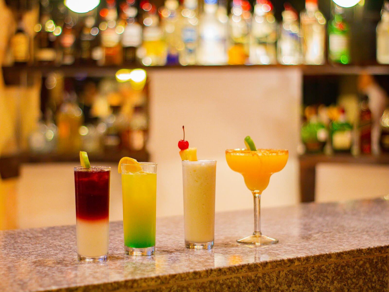 row of mixed drinks at a bar