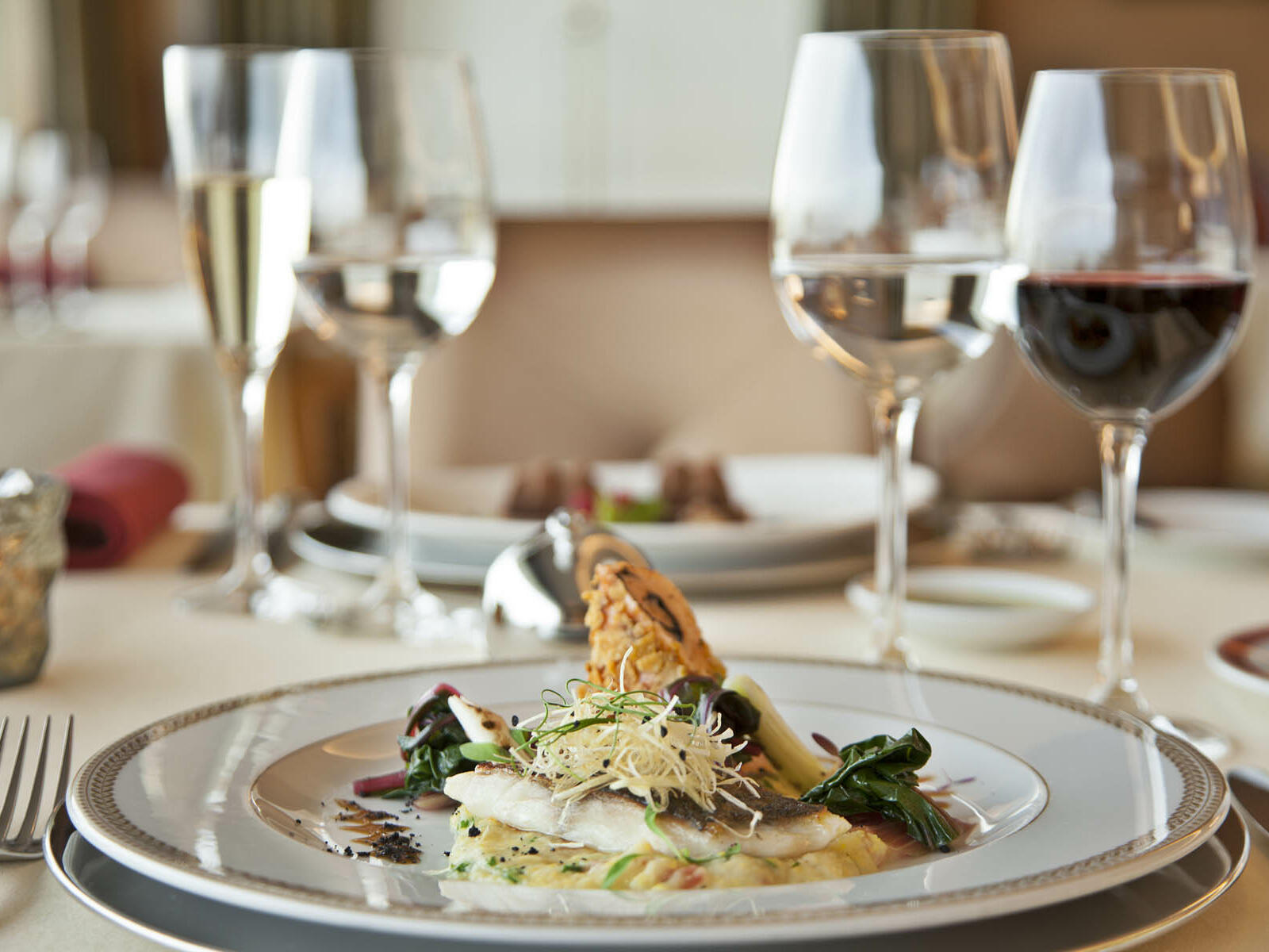 Tasty food with wine glasses kept on the table at Hotel Cascais Miragem Health & Spa