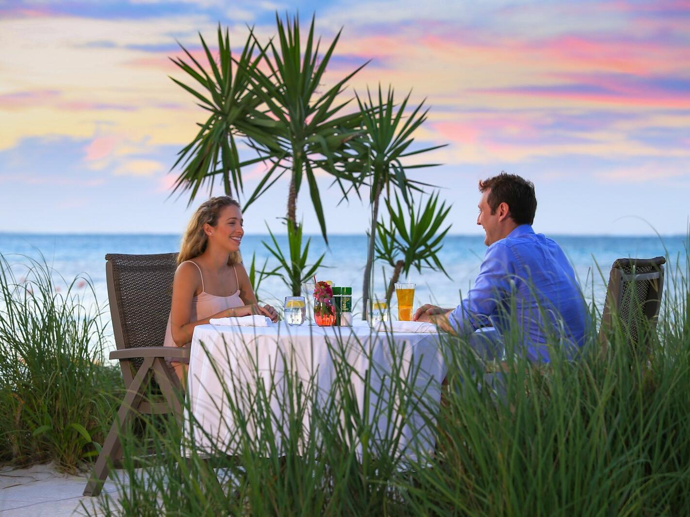Couple enjoying in Dune Beachside Dining at Windsong Resort On The Reef