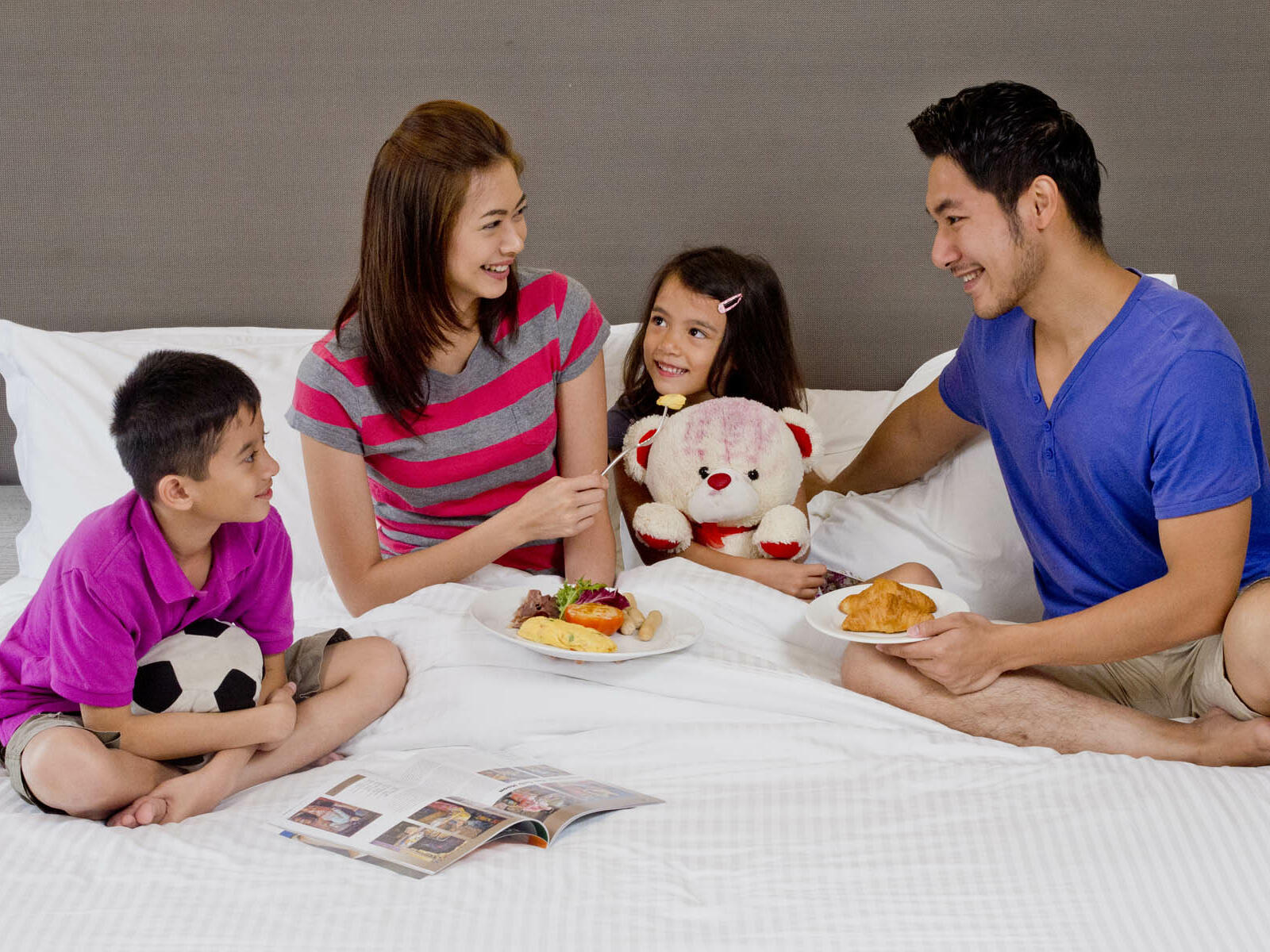 A family enjoying food and company on the bed (Room service)