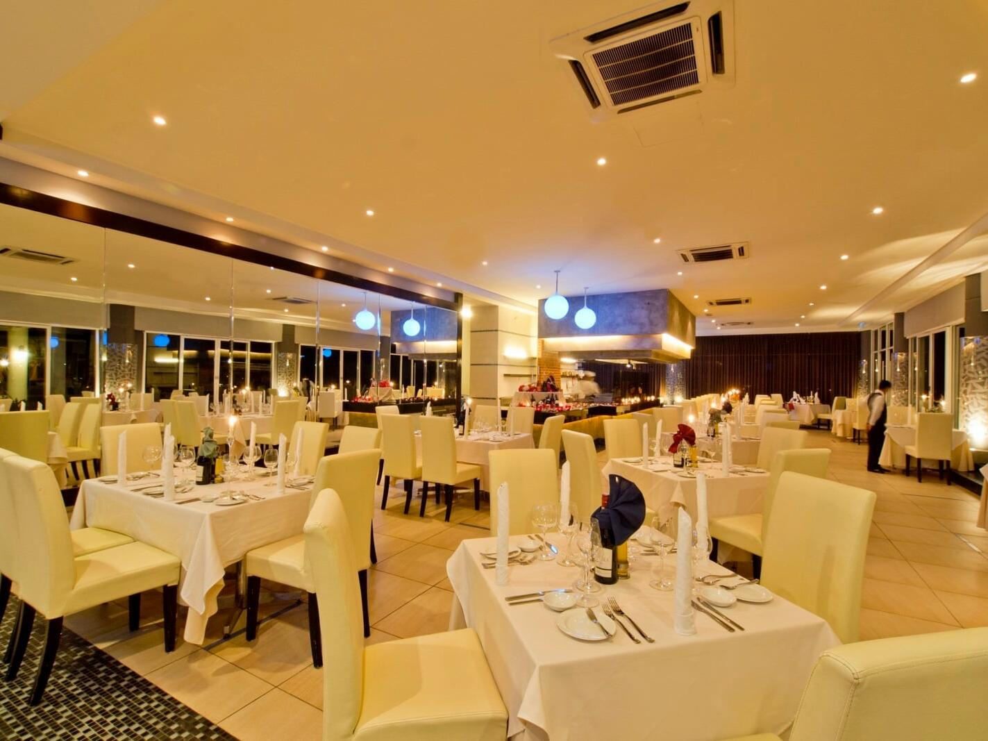 The arranged dining area with white chairs and tables at the Glass Restaurant