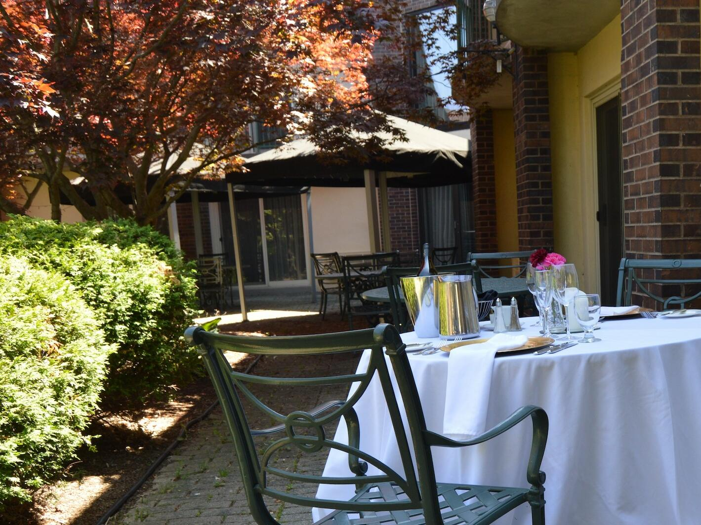 view of dining area with bushes & trees at The Inn of Waterloo