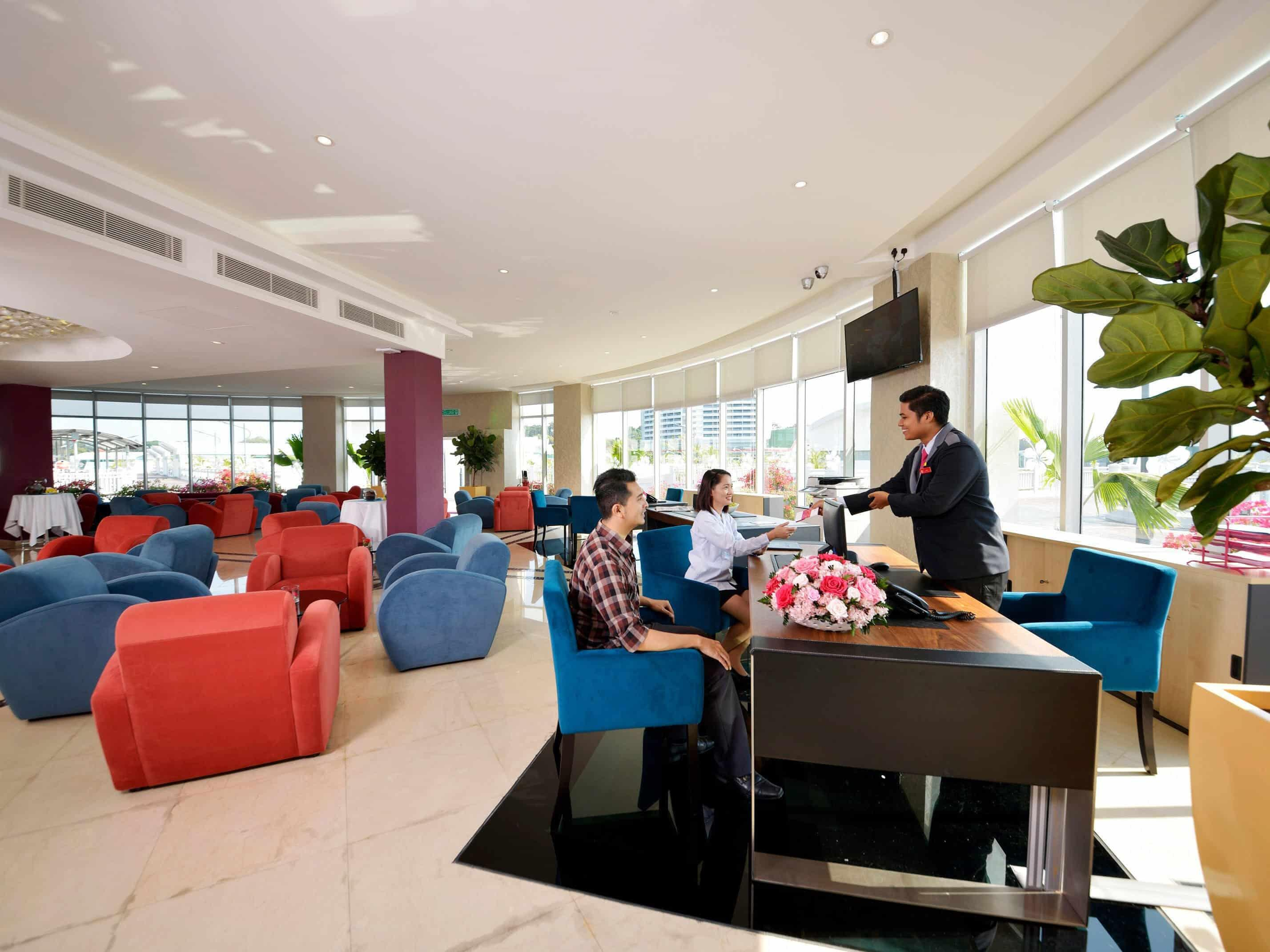 Receptionist passing room key to customers at Captain Lounge, Lexis Hibiscus® Port Dickson