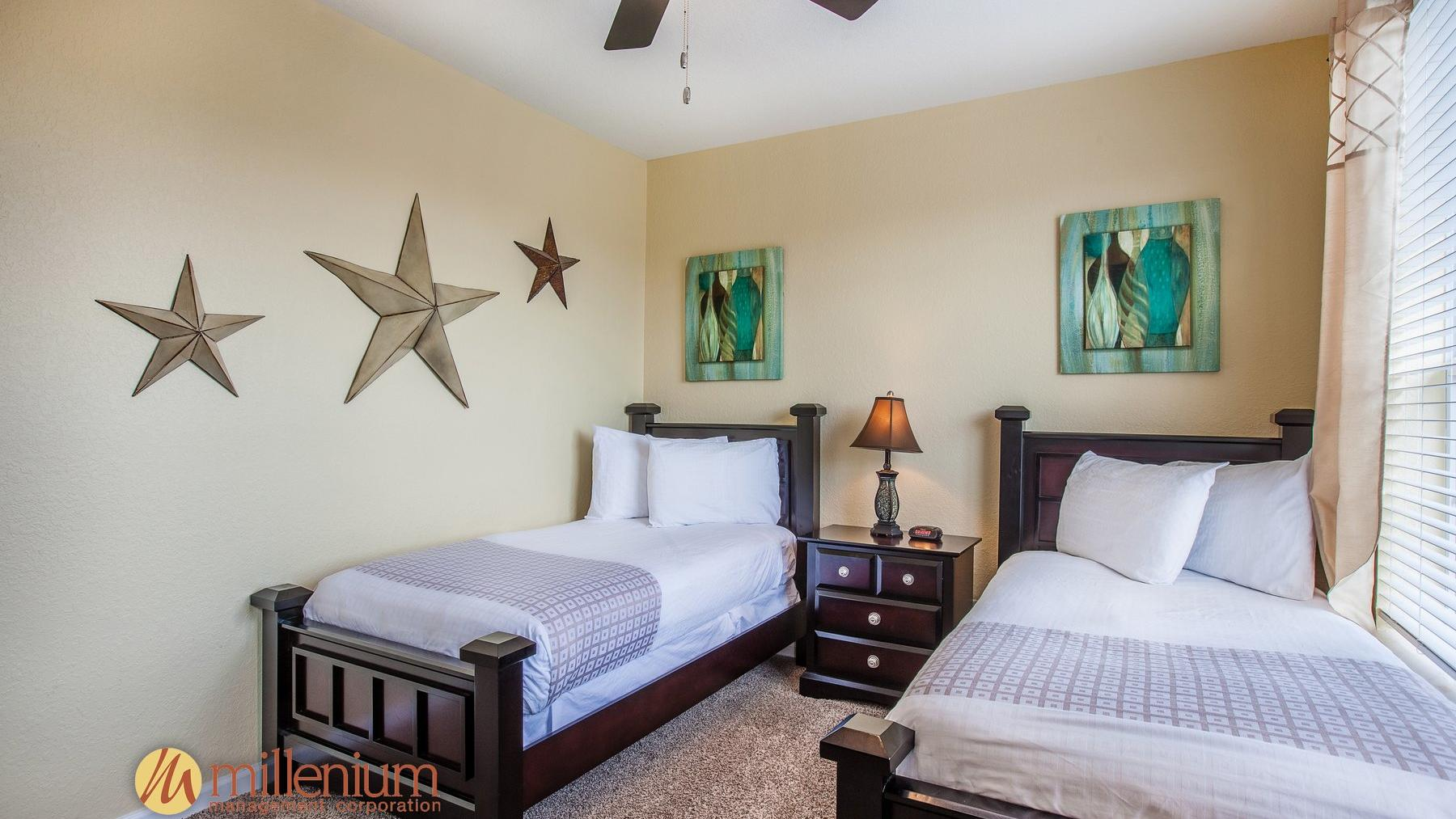 Two twin beds with decorative stars hanging on wall