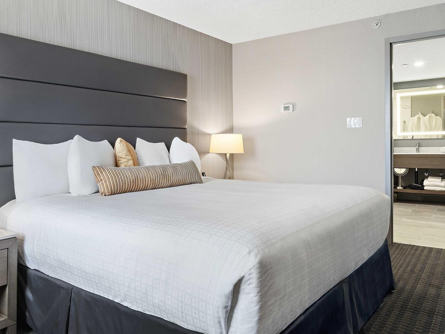 bed in modern hotel room with door to bathroom
