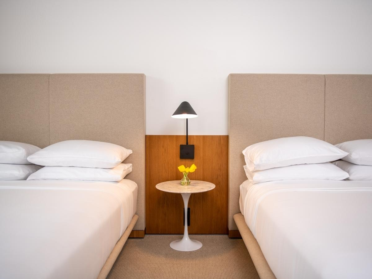 room with two beds and nightstand in between beds