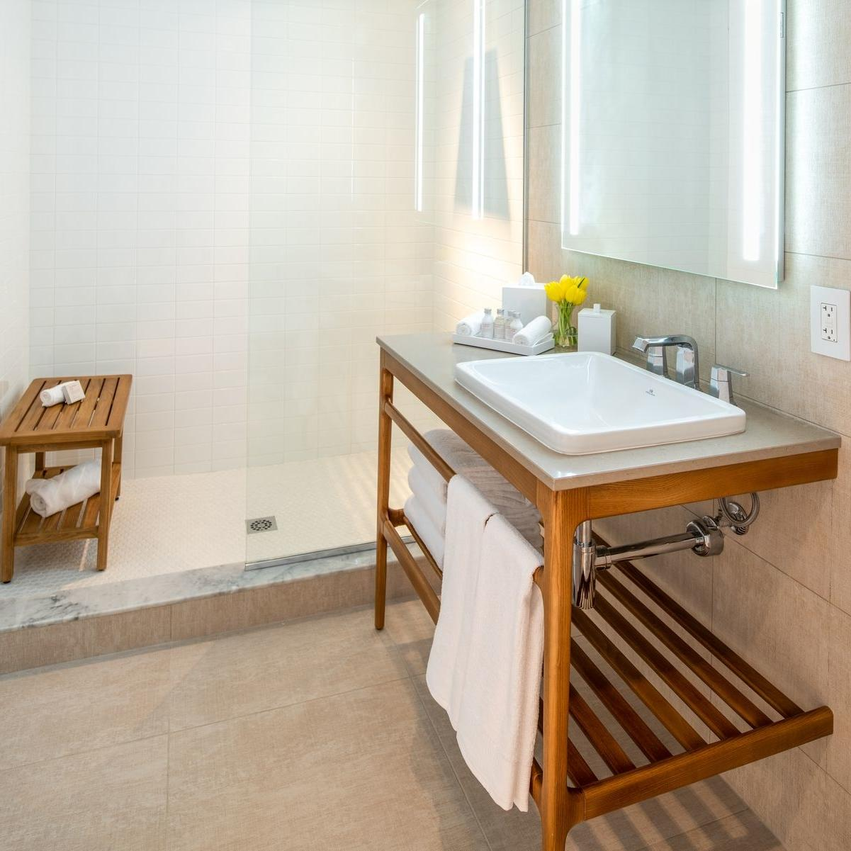 bathroom vanity and mirror with walk in shower