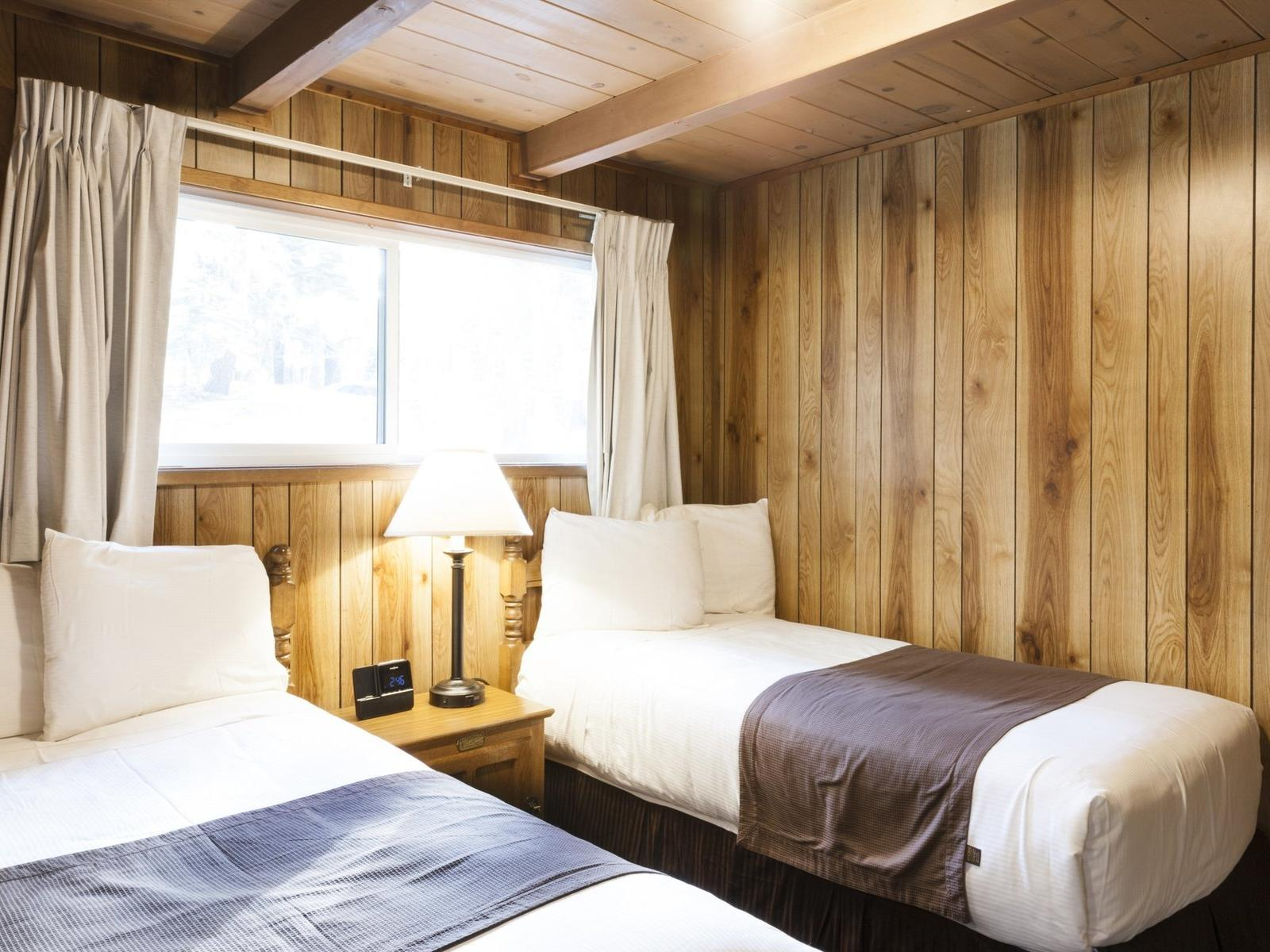 room with two twin beds and nighstand near window
