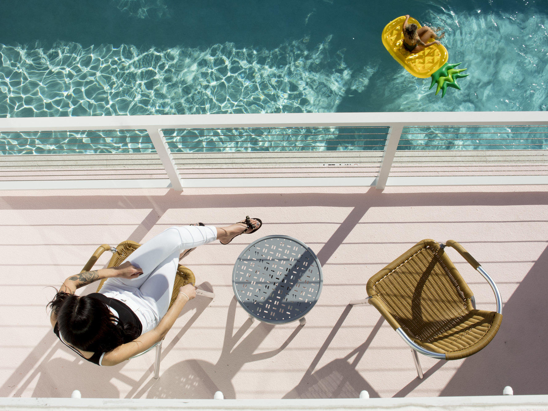 woman sitting on balcony looking down at pool