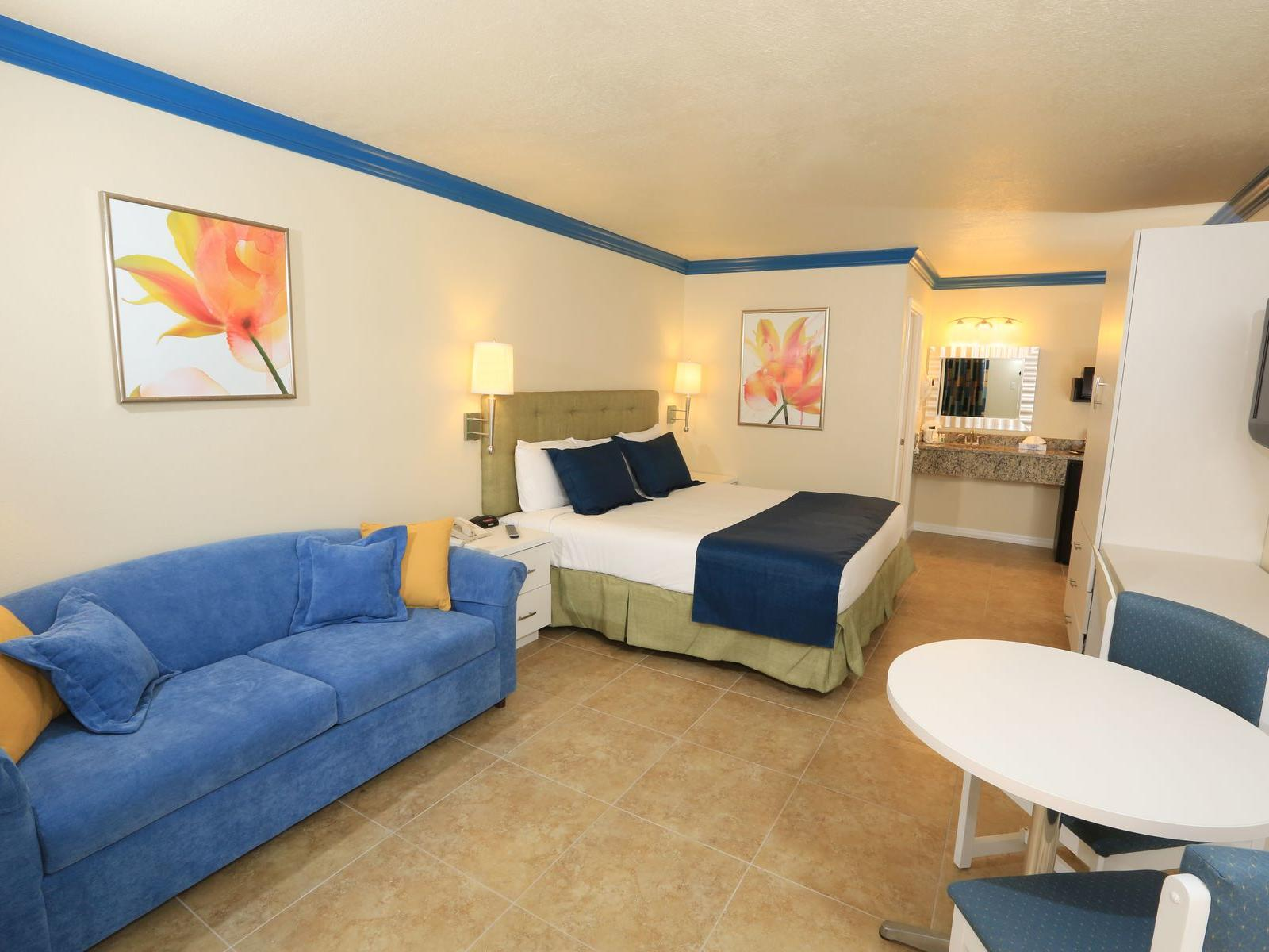 king bed in hotel suite with blue couch